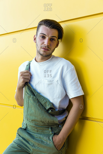 Isolated portrait of a young modern man wearing a green overall and white t-shirt in front of a yellow wall