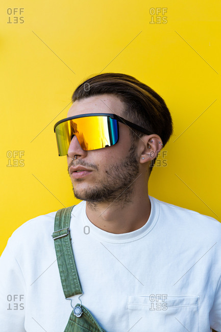 Isolated portrait of a young modern man wearing futuristic rainbow sunglasses, white t-shirt and a green overall in front of a yellow wall