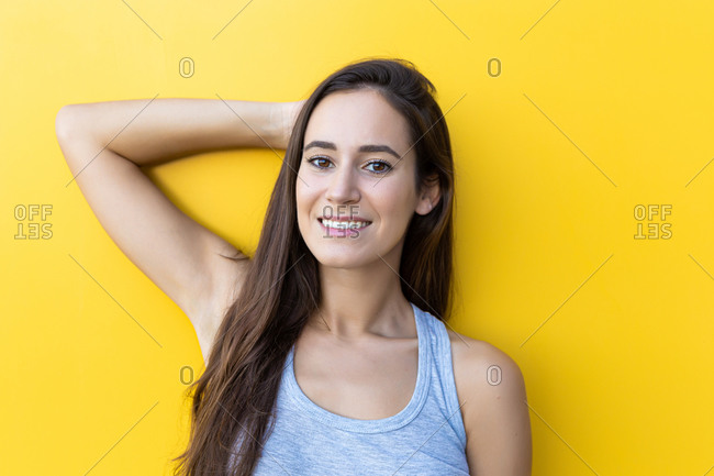 Isolated portrait of a beautiful young woman smiling and wearing denim shorts in front of a yellow wall