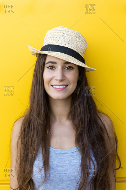 Isolated portrait of a beautiful young woman smiling and wearing a straw summer hat in front of a yellow wall