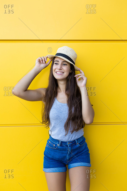 Isolated portrait of a beautiful young woman smiling and wearing denim shorts and straw summer hat in front of a yellow wall