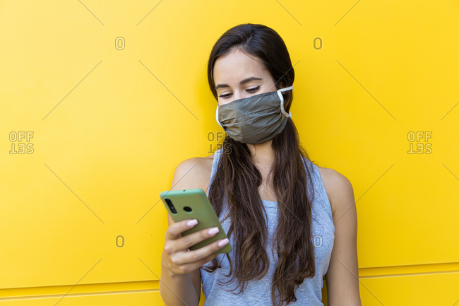 Isolated portrait of a beautiful young woman wearing a gray face mask using her smartphone in front of a yellow wall