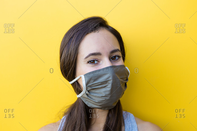 Isolated portrait of a beautiful young woman wearing a gray face mask  in front of a yellow wall