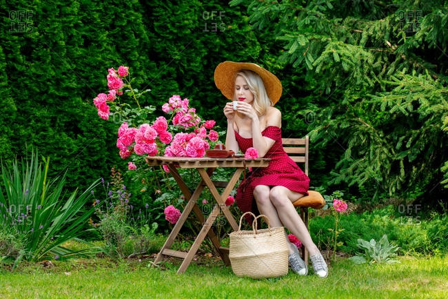 Beautiful blonde girl in red dress drinking a coffee in a garden
