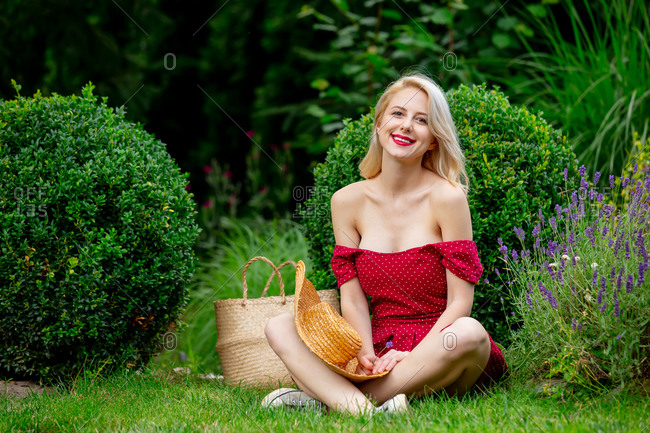 Beautiful blonde girl in red dress in a spring time garden