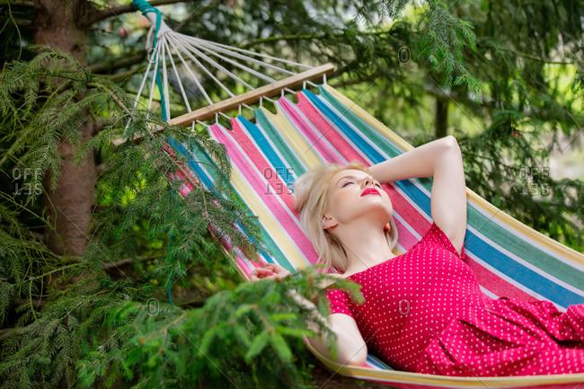 Blonde is lying in a hammock between the fir trees