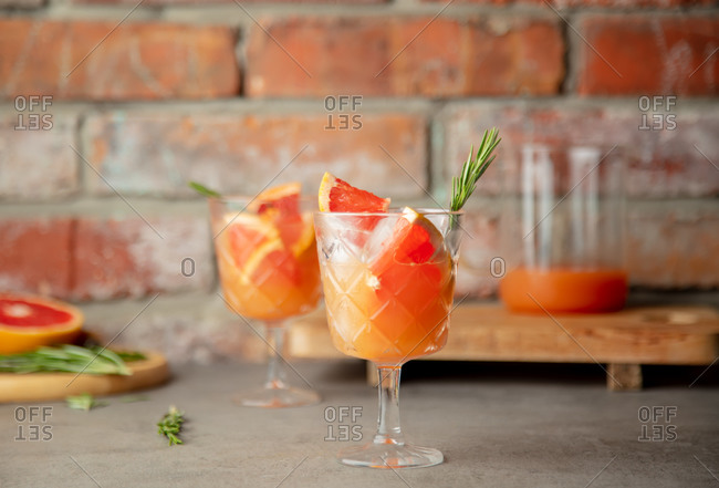 Cocktail with red orange, alcohol, rosemary and ice in a glass on a table.