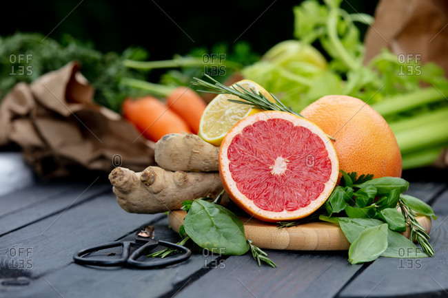 Fresh red orange, parsley, celery, lemon and ginger with scissors on a table in summer season