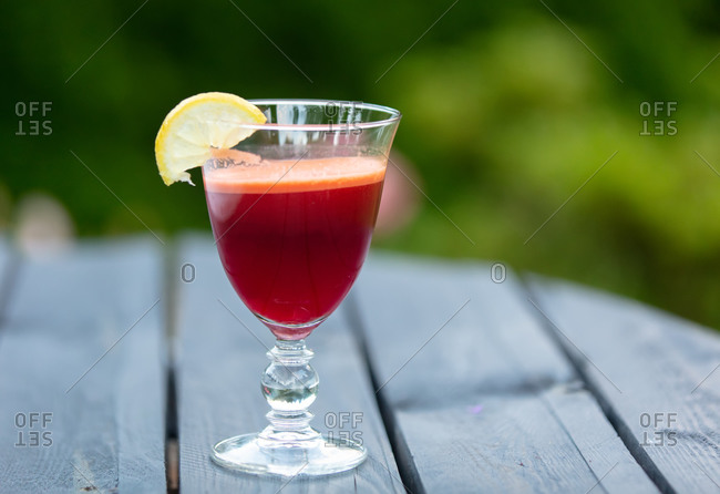 Smoothie with lemon, beet and celery in a glass on a table in a garden