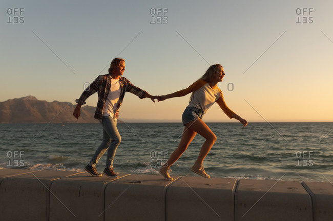 Caucasian couple enjoying their time on a promenade during a sunset