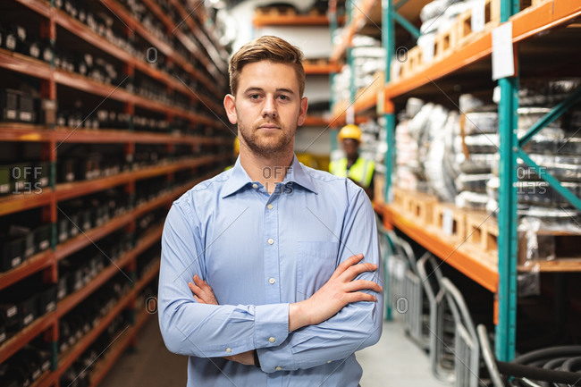 Male factory worker supervisor standing with his arms crossed at the factory