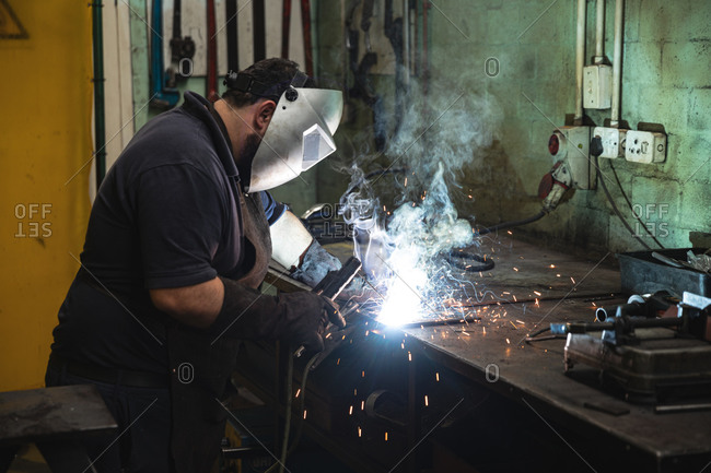 Male factory worker wearing mask welding at the factory