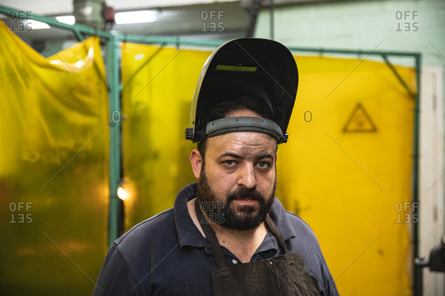 Portrait of male factory worker wearing welding mask at the factory