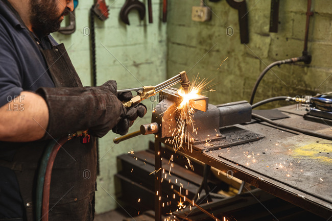 Male factory worker using welding torch at the factory