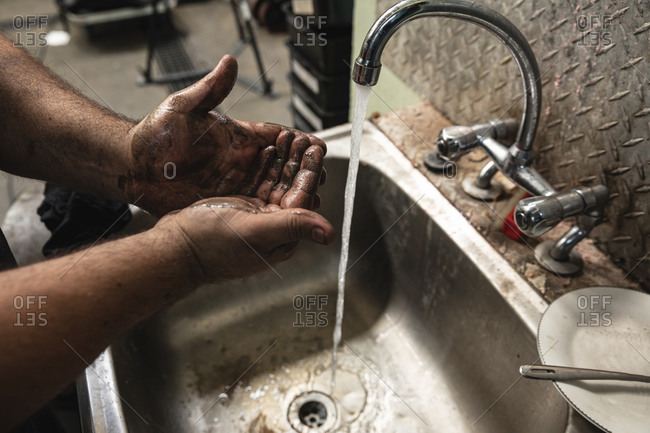 Close-up of a male factory worker washing hands in the sink