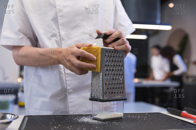 Mid section of chef grating cheese at restaurant kitchen