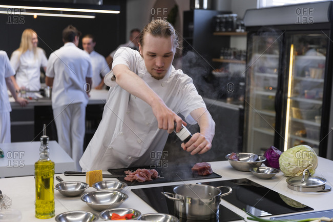 Young male chef adding salt in boiling water at restaurant kitchen
