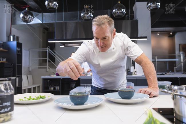 Senior male chef adding salt in a dish at restaurant kitchen