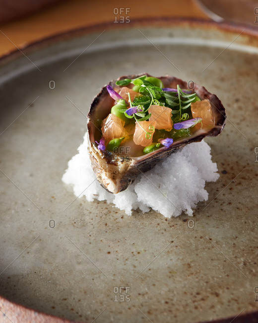Amuse bouche of oyster in it's shell on ice with grapefruit, peas and micro greens with lavender on a large plate