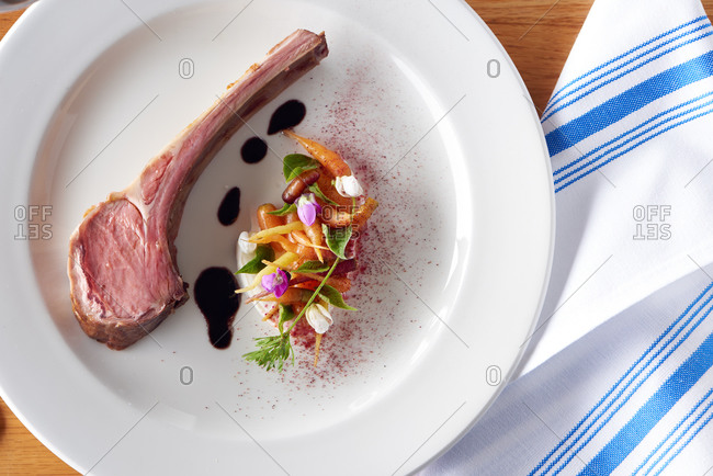 Rare cooked lamb with micro carrots and goat cheese served at an upscale restaurant