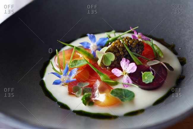 Small appetizer of salmon and caviar with various edible flowers and basil oil in a gray bowl