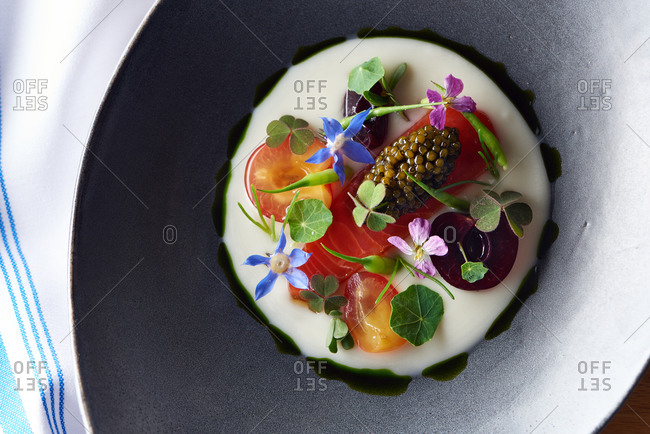 Overhead view of a small appetizer of salmon and caviar with various edible flowers and basil oil in a gray bowl