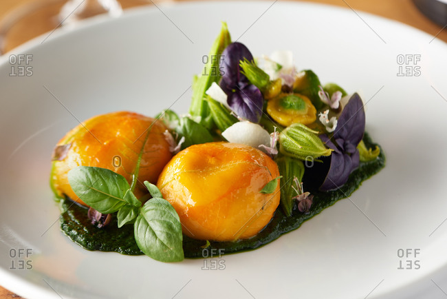 Squash blossom salad over pesto with micro greens and basil served in an upscale restaurant