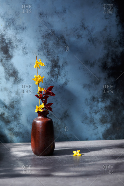 Spring still life of a vase with yellow flowers in dappled afternoon light