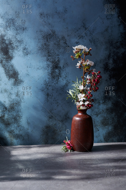Various spring buds and flowers in a vase in dappled afternoon light