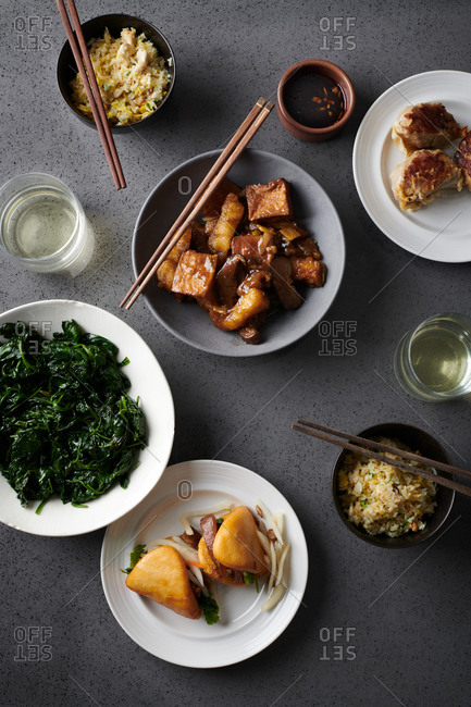 Plated up take out including sauteed spinach, seabass clay pot, dumplings, pork belly sliders and fried rice with white wine, shot from above