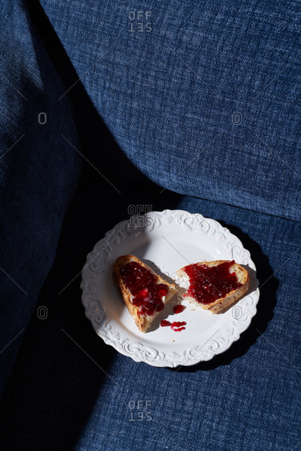 Toast with raspberry jam on a couch in hard light
