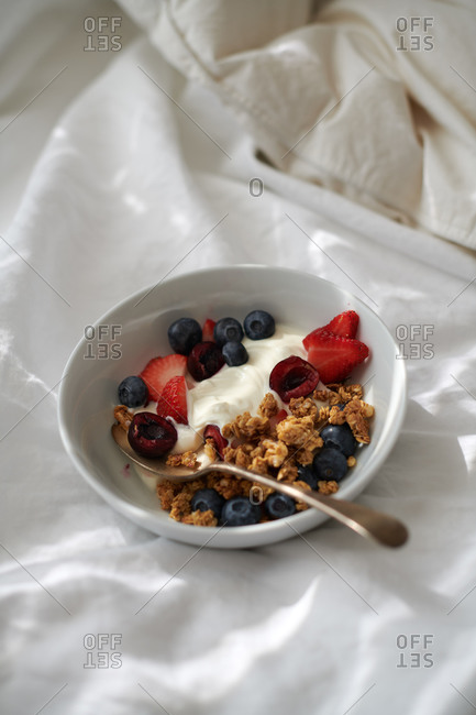 Breakfast in bed with a bowl of granola, yogurt, strawberries, blueberries on white sheets in the morning light