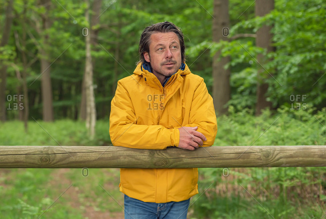 Man wearing yellow jacket leaning on wooden fence rail in the country