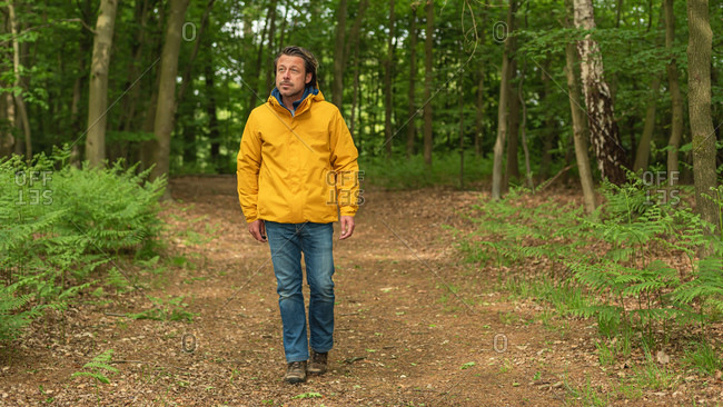 Man wearing yellow jacket walking on a path in the woods