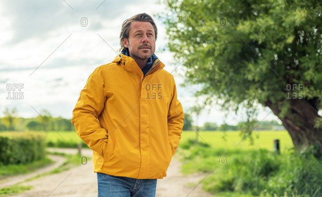 Man wearing yellow jacket walking on a path in the country