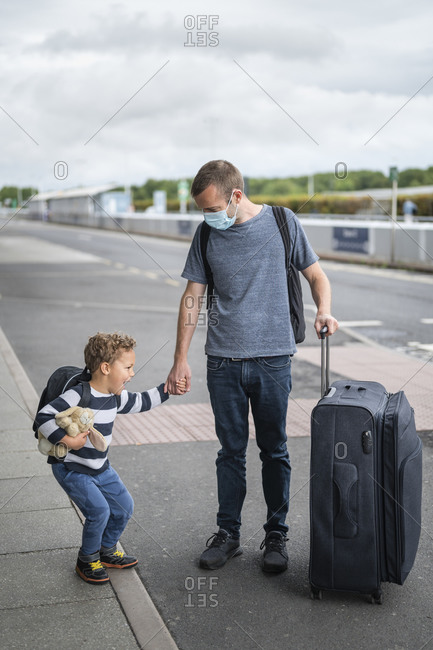 Father and son arriving at empty airport during pandemic