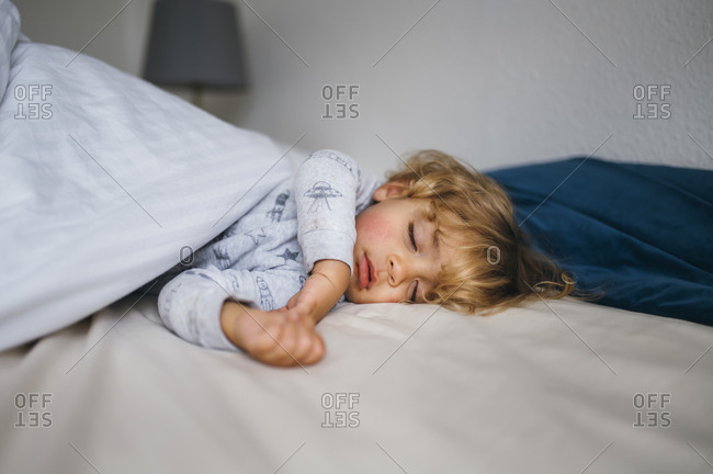 Young child asleep on bed