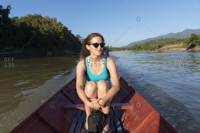 Tourist riding in a wooden speed boat on the Nam Khan River, Luang Prabang, Laos