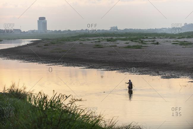 Vientiane, Laos - November 30, 2014: Fisherman in the Mekong River at dusk