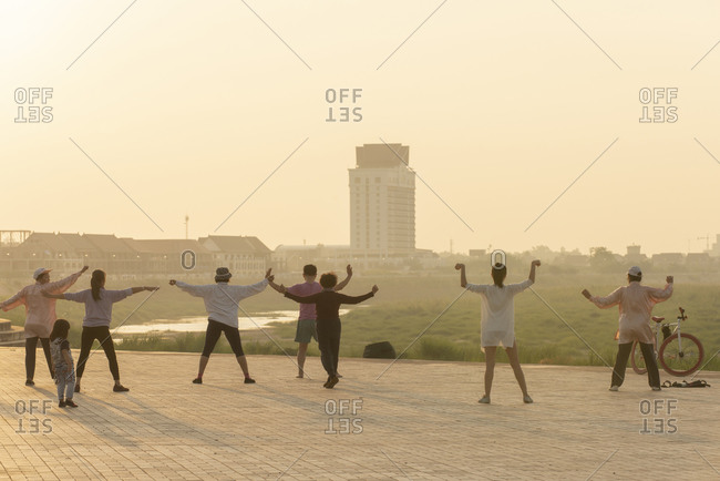 Vientiane, Laos - November 30, 2014: Group of people exercising along the Mekong River at sunrise