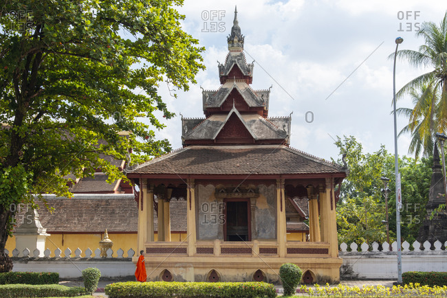 Vientiane, Laos - November 30, 2014: Buddhist monk walking in front of the Sisaket Temple in Vientiane