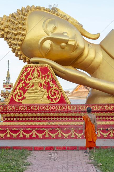 Vientiane, Laos - November 30, 2014: Monk looking at the reclining Buddha at Wat That Khao
