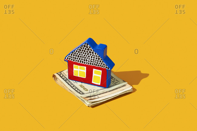 Toy house on a pile of US dollar banknotes on a yellow background