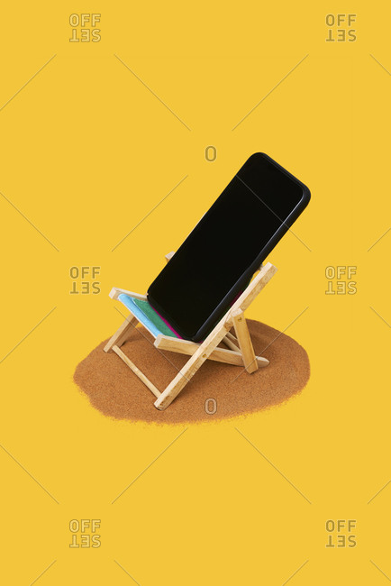 Smartphone in a small deck chair on a pile of sand on a bright yellow background