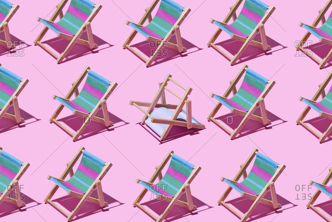 Blue and pink striped deck chairs on a pink background with one upside down in the center