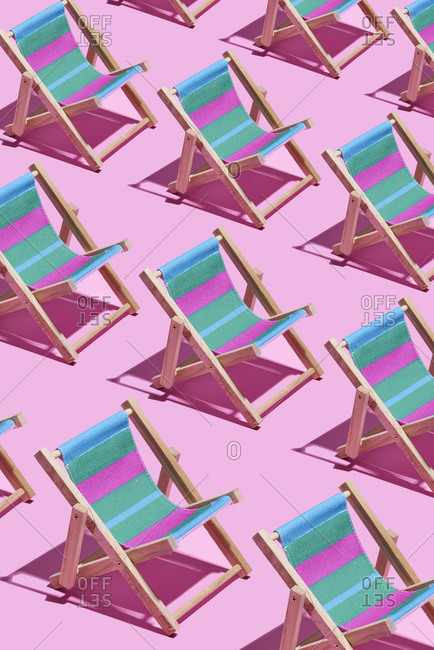 Blue and pink striped deck chairs on a pink background