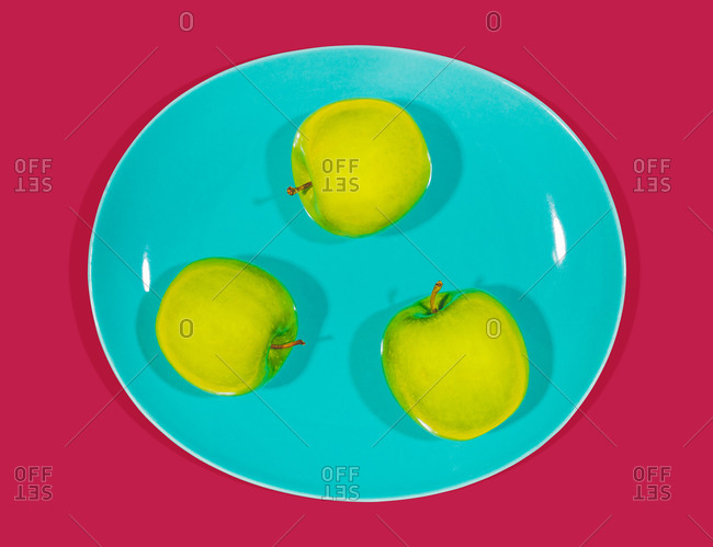 Bright green apples on a blue plate on maroon background