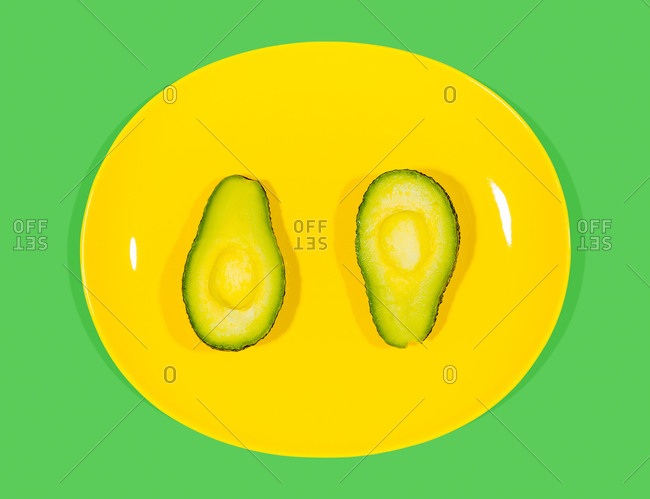 An avocado sliced in half on a yellow plate on green background