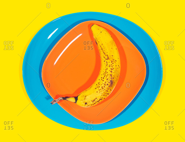 A banana on stacked colorful plates