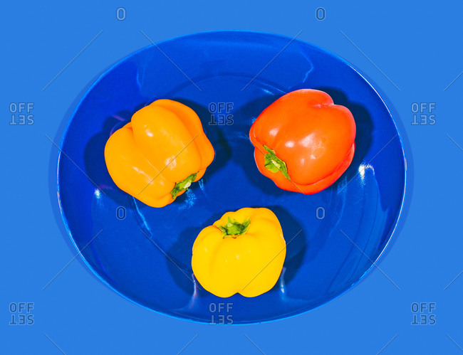Colorful sweet peppers on a blue plate and blue background